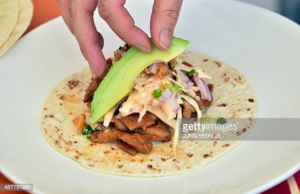 A chef makes Korean style tacos during the Hansik Week for the Korean food culture in Seoul on October 24 2014 AFP PHOTO / JUNG YEONJE
