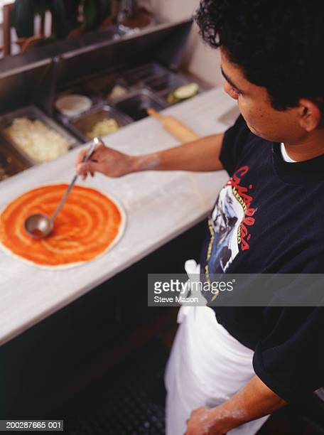 Chef making pizza on table in kitchen