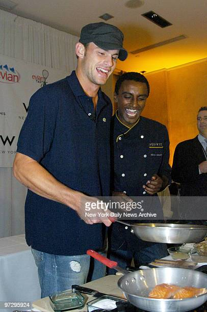 Chef Marcus Samuelson of the restaurant Aquavit helps tennis star Andy Roddick prepare a salmon dish during the sixth annual Evian Taste of Tennis...
