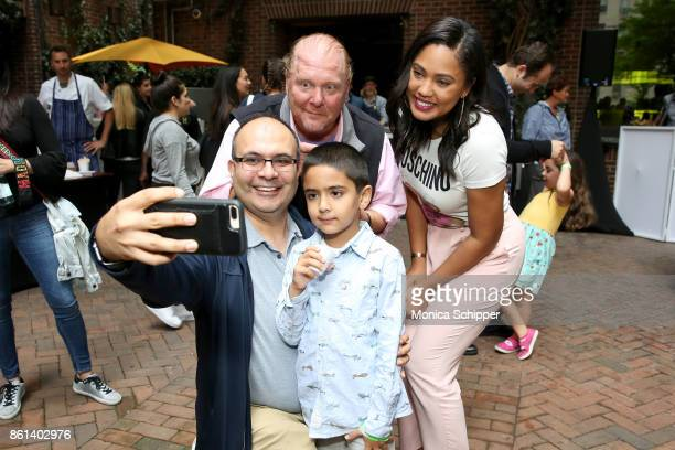Chef Mario Batali and Ayesha Curry pose for a selfie with guests during Family Ice Cream Fundae hosted by Mario Batali and Ayesha Curry at Private...