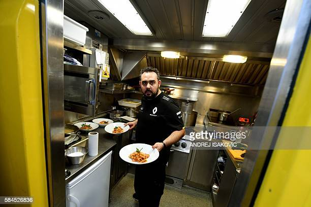 Chef Massimiliano Portioli holds plates as he cooks meals for the F1 Renault crew ahead of the Formula One Hungarian Grand Prix at the Hungaroring...
