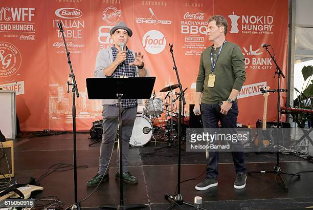 Chef Michael Symon and Chef Bobby Flay speak onstage at the CocaCola Backyard BBQ hosted by Bobby Flay and Michael Symon presented by Thrillist...
