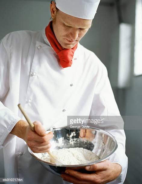chef mixing flour in a bowl in the kitchen