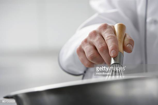 Chef mixing ingredients in bowl close-up