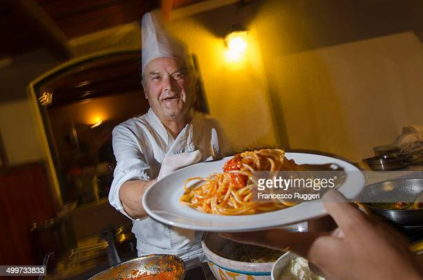 Chef offering spaghetti with tomato sauce