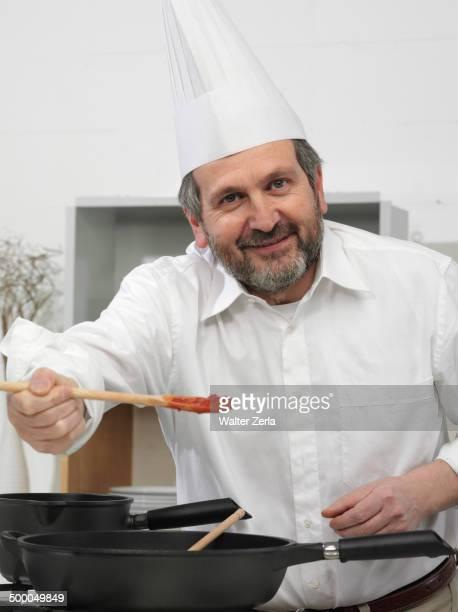 Chef offering taste of food in kitchen