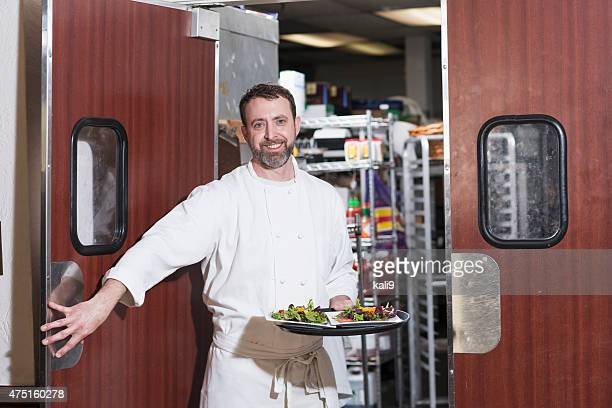 Chef or waiter in restaurant carrying tray of food