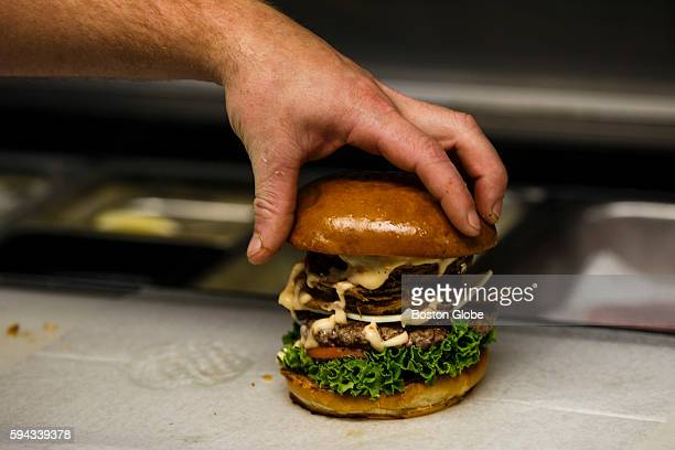 A chef places a bun on top of an Obama Burger at John's Fish Market in Vineyard Haven Mass on the island of Martha's Vineyard Aug 18 2016 President...