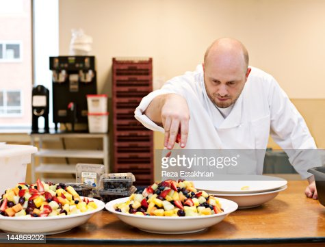 Chef places final touches to fruit salad : Stock Photo