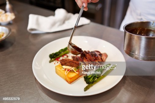 Chef pouring sauce on dish in the kitchen