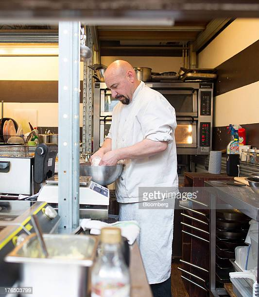 A chef prepares food in a restaurant kitchen in Brixton Village in London UK on Wednesday Aug 14 2013 UK services growth accelerated more than...