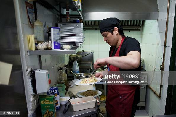 A chef prepares plates for the lunch of paying clients during the day at Robin Hood restaurant on December 5 2016 in Madrid Spain Association...
