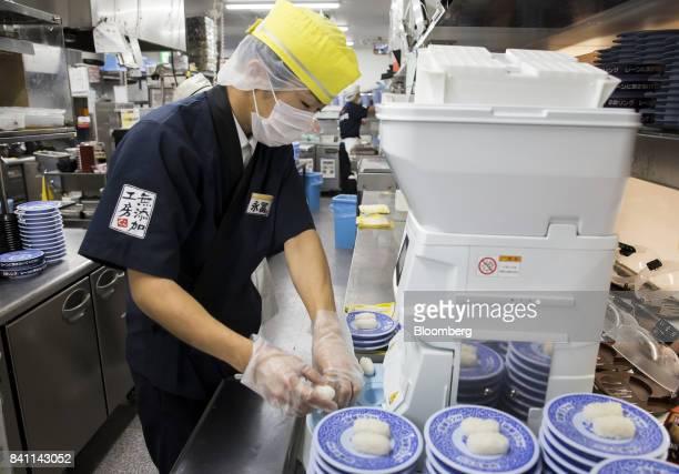 A chef prepares sushi using a Suzumo Machinery Co sushimaking machine inside a Kura Corp sushi restaurant in Kaizuka Osaka Japan on Thursday Aug 17...