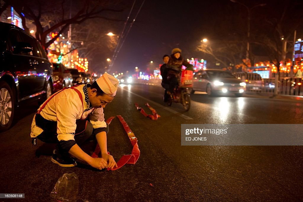A chef prepares to light firecrackers on a street in Beijing during the lantern festival, which marks the end of celebrations for the Chinese new year period, on February 24, 2013. China celebrated the traditional lantern festival with food and fireworks as millions of migrant workers flowed back to the cities and smog blanketed a large part of the country. AFP PHOTO / Ed Jones