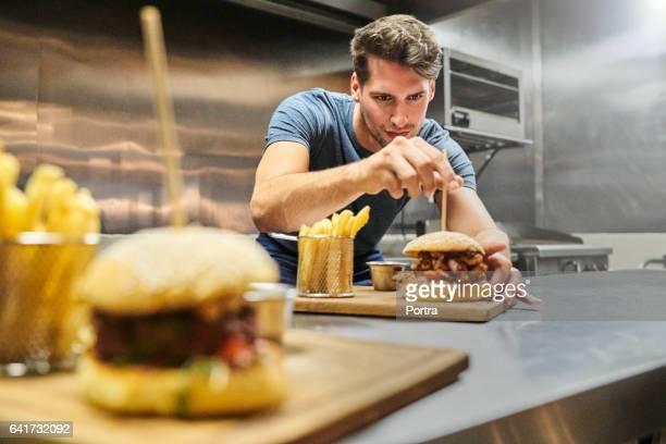 Chef préparation hamburger sur plaque au restaurant