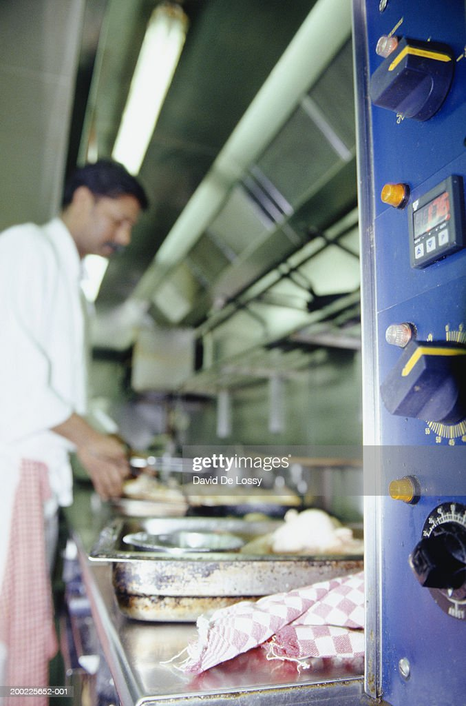 Chef preparing food in kitchen, side view : Stock Photo