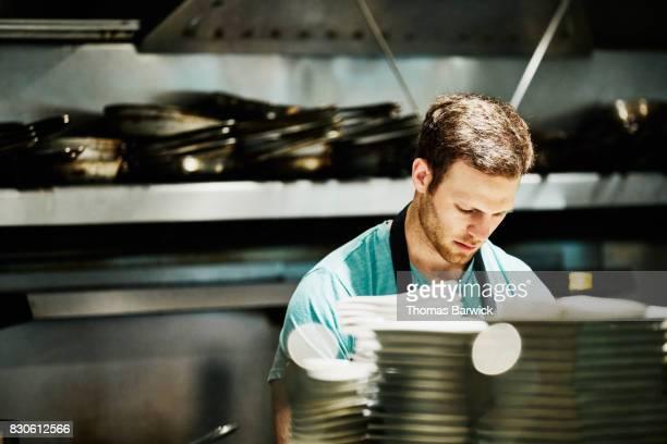 Chef preparing for evening dinner service in restaurant kitchen