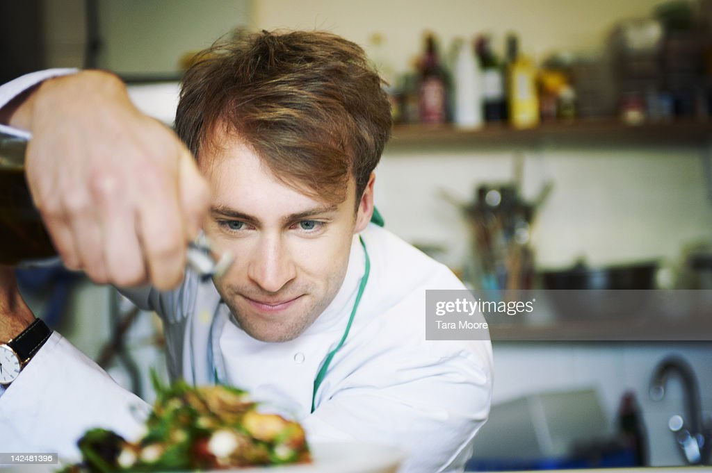 chef preparing meal in restaurant : Stock Photo