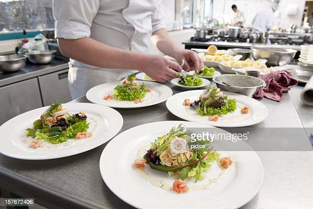 chef preparing white plates with seafood salad