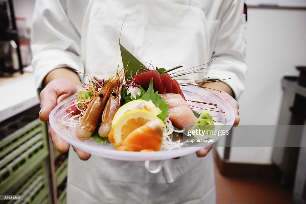 Chef presenting sashimi plate