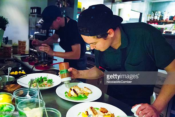 Chef putting finishing touches to plating his dishes