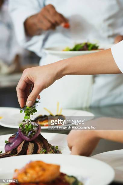 Chef putting garnish on plate of food