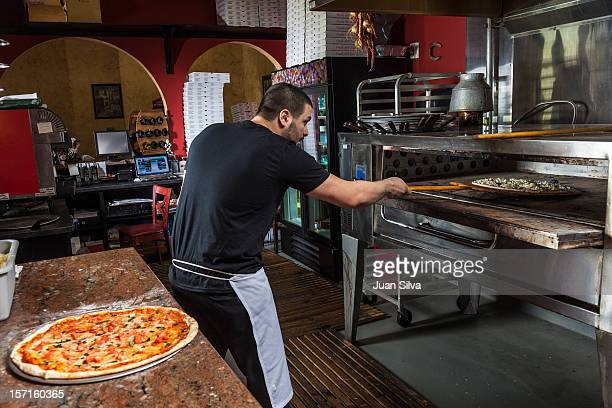 Chef putting pizza in the oven in a restaurant
