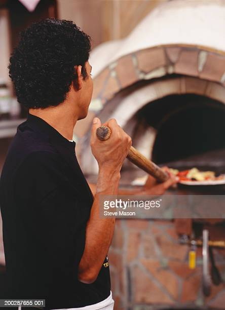 Chef putting pizza into stove