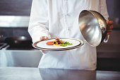 Chef raising a bell of a dish in commercial kitchen