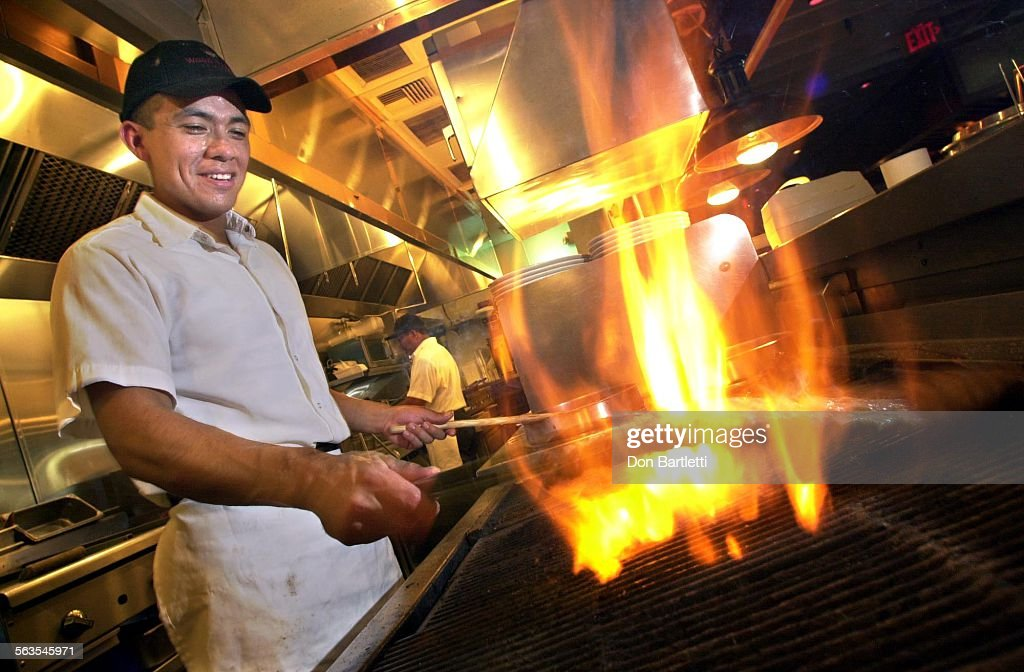 Chef Rodrigo Jasso grills an order of ribs over mesquite flames at the Wood  Ranch BBQ - Chef Rodrigo Jasso Grills An Order Of Ribs Over Mesquite Flames At
