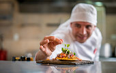 Portrait of a chef serving a plate at a restaurant and decorating it in the kitchen - focus on foreground