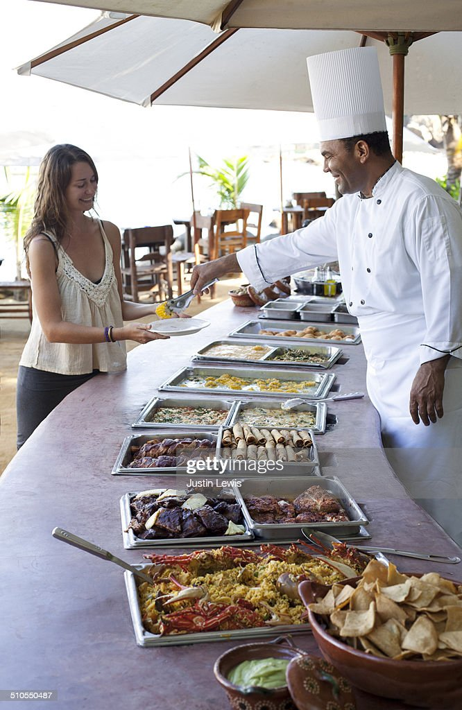 Chef serving guest in outside buffet