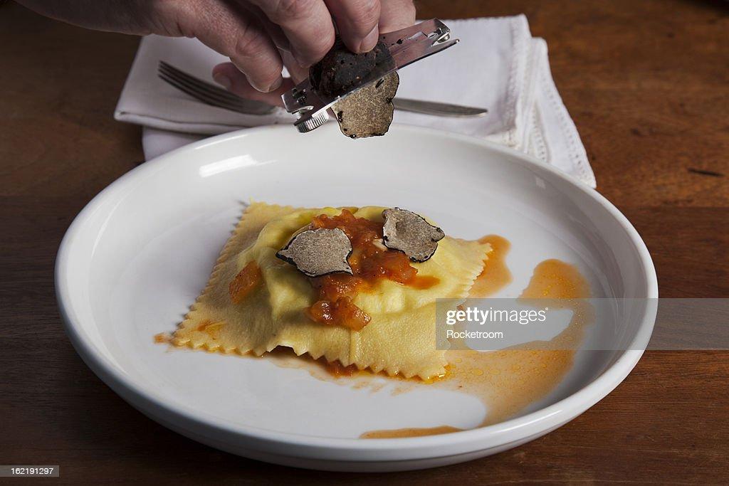 Chef shaving black truffles onto ravioli : Stock Photo