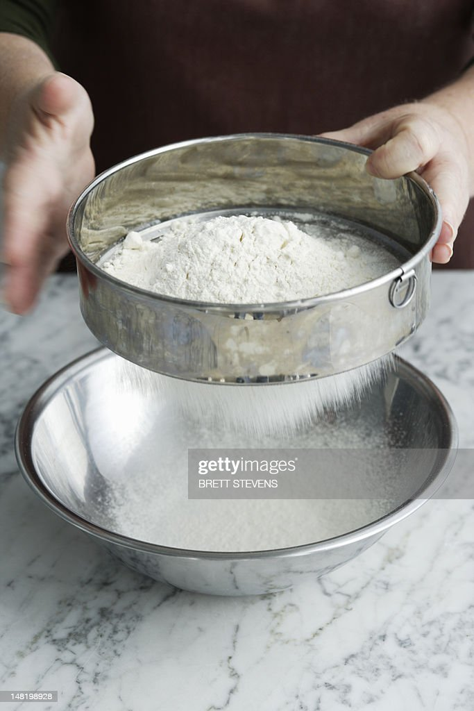 Chef sifting flour in bowl