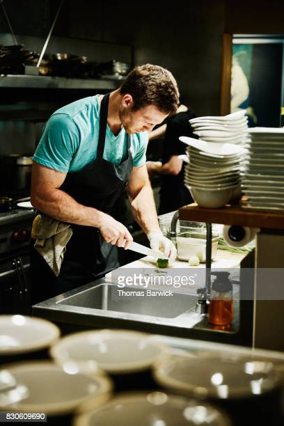 Chef slicing limes while preparing for evening meal service in restaurant kitchen