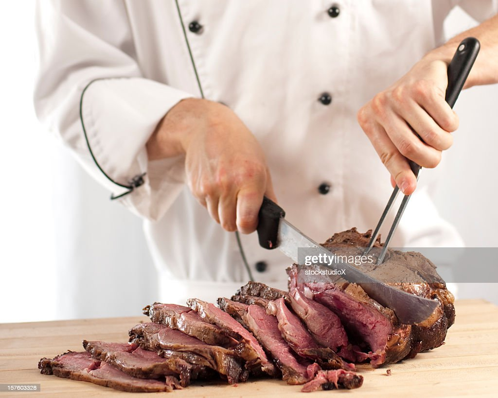 Chef slicing roast beef using carving knife and fork