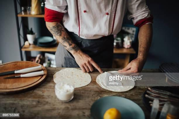 Chef smear cream on tortilla