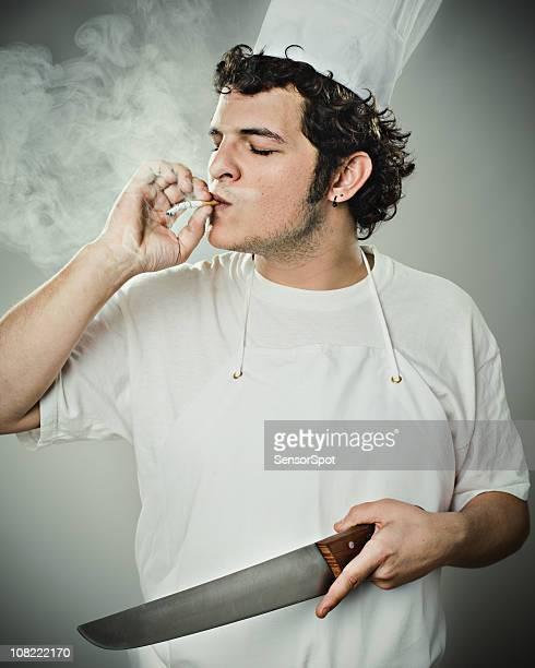 Chef fumeur et tenant un couteau