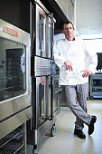 Chef standing by oven in restaurant kitchen, portrait