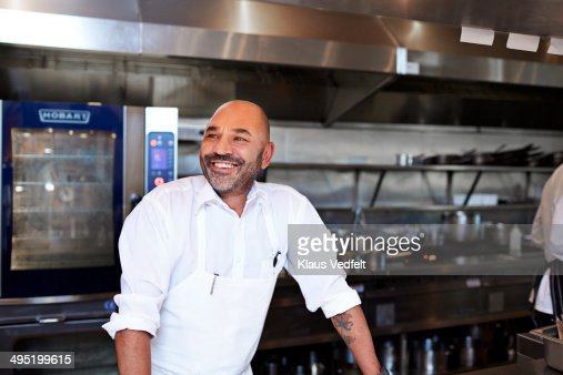 Chef standing in kitchen laughing