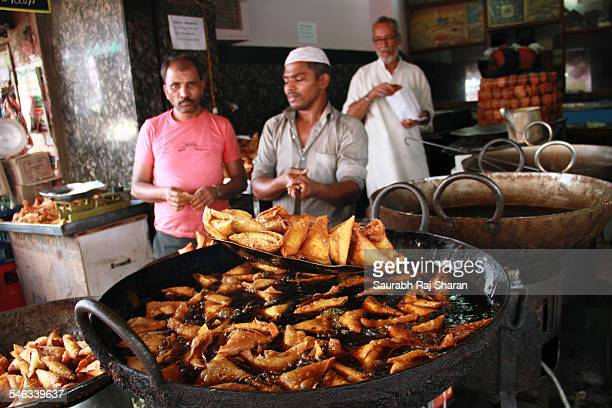 Chef taking the samosa out of frying pan in Bangalore