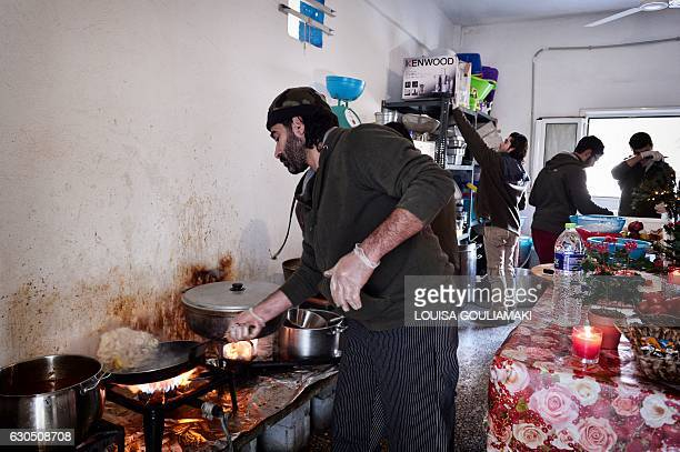 Chef Talal Rankoussi and other Syrian volunteers prepare a meal in 'cafe Rits' in Ritsona refugee camp some 80 km north of Athens on December 21 2016...