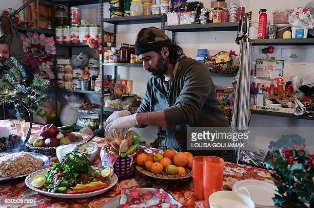 Chef Talal Rankoussi puts final touch to the prepared meal in the 'cafe Rits' in Ritsona refugee camp some 80 km north of Athens on December 21 2016...