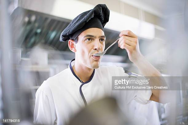 Chef tasting food in kitchen