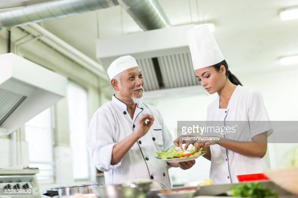 Chef teaching a trainee to prepare asian food