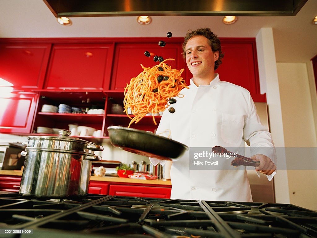 Chef tossing spaghetti and olives from pan : Stock Photo