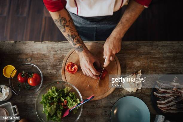 Chef uses the knife to slice tomato into smaller pieces for salad