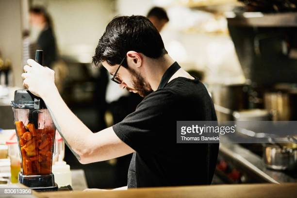 Chef using blender for dinner preparation in restaurant kitchen
