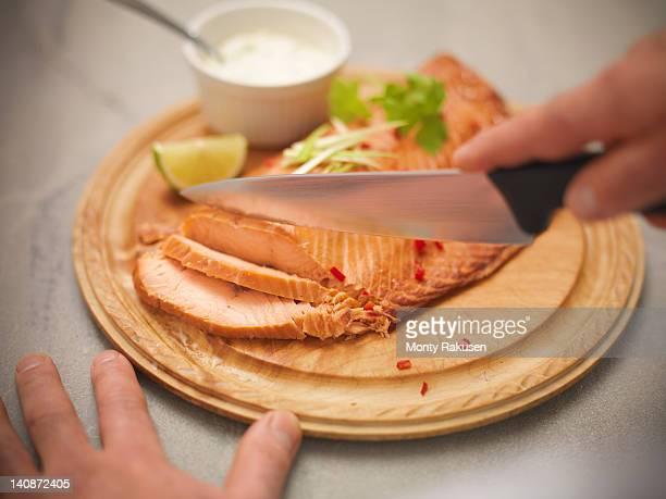 Chef using knife to slice hot-smoked Scottish salmon on board