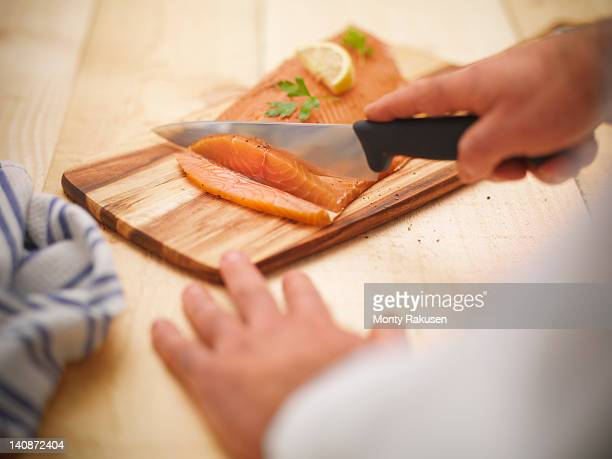 Chef using knife to slice Scottish smoked salmon on board